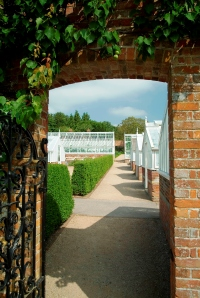 Glasshouses at West Dean through archway